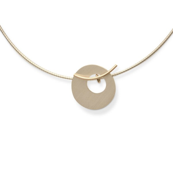 DISC NECKLACE Designer Jewellery. This unique disc jewellery comprises a 2cm silver disc which is suspended on a curved gold line. This allows the wearer to select whether to wear the line curving up or curving down. The designer jewellery pendant can either have a 16 or 18 inch silver omega necklace.