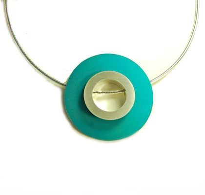 The geometric disc pendant necklace features a bold anodised aluminium disc that is interchangeable with a variety of colours to suit you.