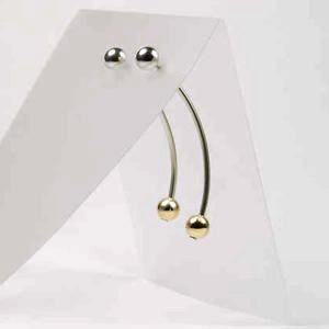 These highly polished silver earrings with 7mm 9ct gold ball are 5.5cm long. The ball lies in front of your ear and the long section hangs down behind.