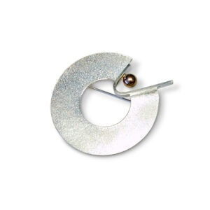 Textured metal brooch with 9ct gold ball. This brooch is approx. 4.5 cm in diameter and plays with the subtle contrasts of colour and texture. The brooch has a silver stamp 925