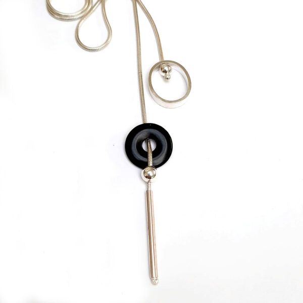Contemporary lariat style black onyx necklace. The  front fastening mechanism makes it so easy to wear and creates the unique design feature of a circle and a doughnut shaped stone balancing on a ball at the front.
