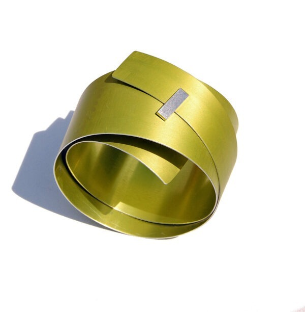 large, lime aluminium bangle with rectangular silver detail at the front