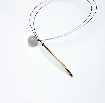 The Necklace in brass, steel and quartz has a unique fastening incorporated into the design