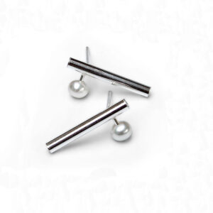 Bar-and-pearl-earring. A stud style of earring comprising a 15mm silver bar with a 5mm cultured pearl protruding from the side of the bar as it sits on the ear lobe