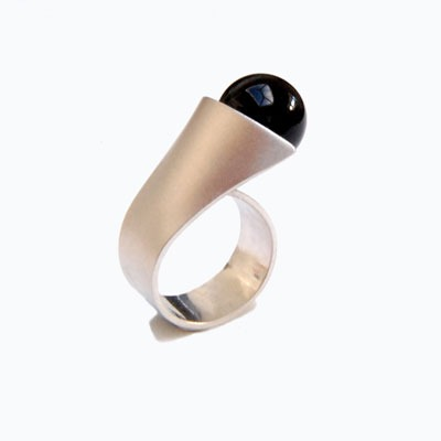 Silver ring with a large black onyx bead. This Statement ring will get you noticed. It slips onto your finger and the bead leans over and rests on your adjacent finger. The black bead contrasts beautifully with the with textured or polished silver