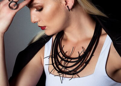 Model wearing Helen Swan Necklace and rings with a white top