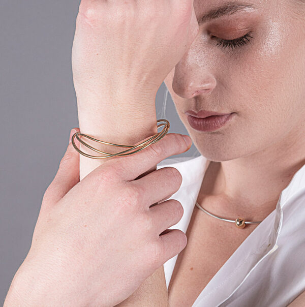 circle stacking bangle which is made of one continous loop of material modelled on a wrist which is held by a hand