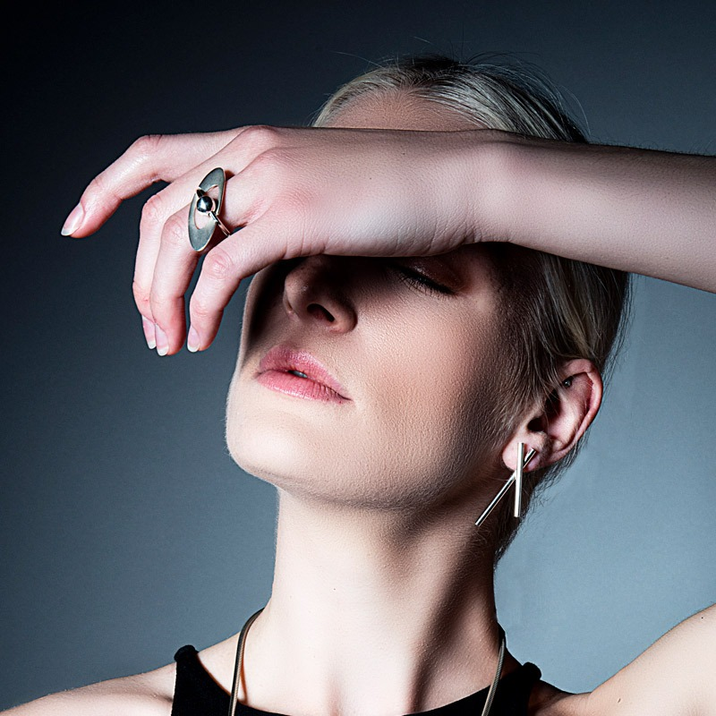 A model is shown wearing a modern engagement ring which is handmade with silver and gold by designer Helen Swan.