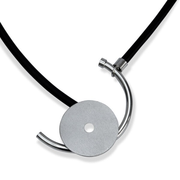 Rubber and 925 white metal. Front fastened necklace with a disc and curved bar
