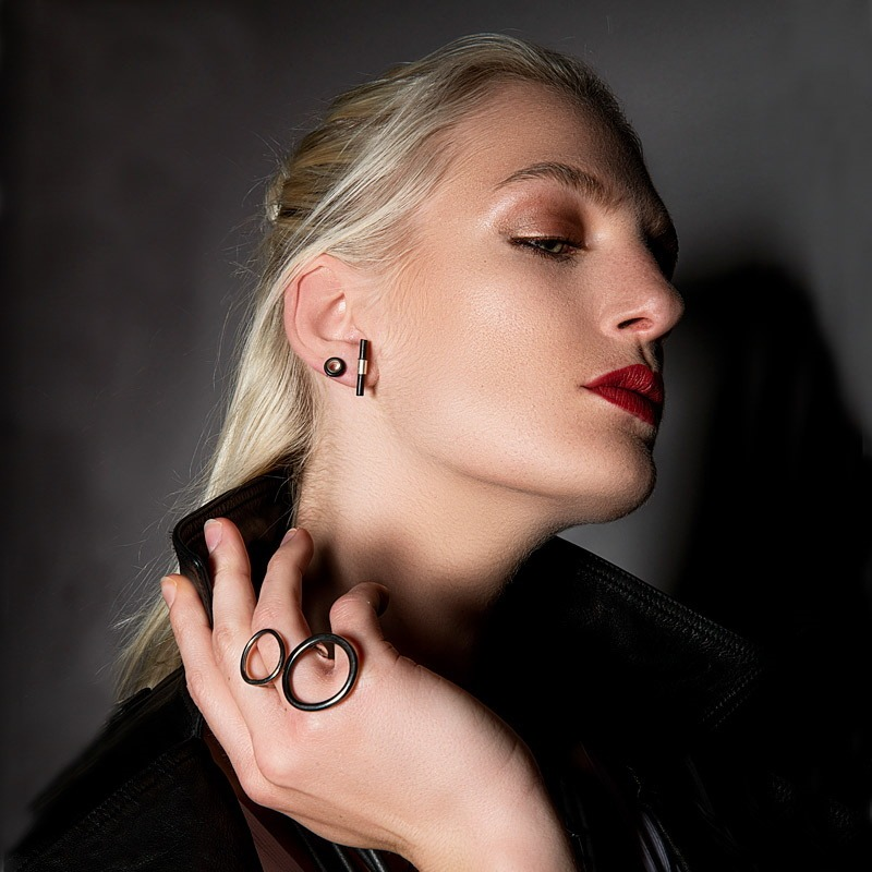A blonde model is shown wearing contemporary earrings which are made of rubber and silver along with a set of hammered rings.