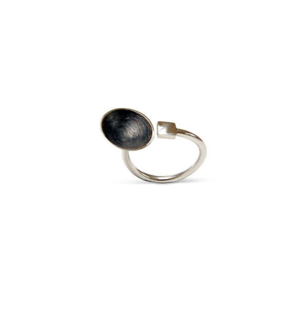 Cup and Cube Textured Ring is displayed on a white background and features a polished metal ring with a oxidised black dome next to a polished cube handmade by Helen Swan Designer Jewellery