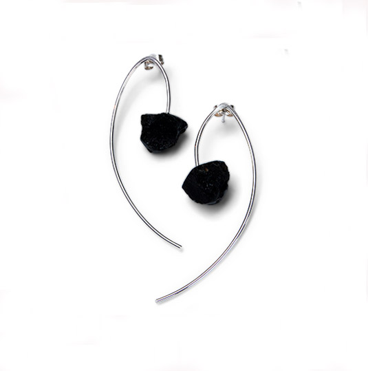 A pair of long silver drop earrings with a hanging lava rock pendant designed by Helen Swan Jewellery